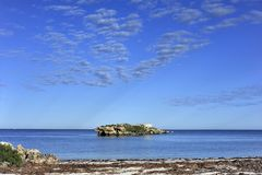 Sunlight on a Solitory Island with calm ocean, and Clear Sky. stock photos
