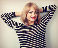 Beautiful calm blond hair style woman resting near the wall Stock Photos