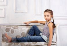 Beautiful calm happy kid girl sitting on the bench in blue jeans Royalty Free Stock Images