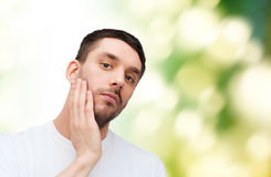 Beautiful calm man touching his face Stock Photos