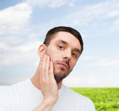 Beautiful calm man touching his face Royalty Free Stock Photos