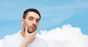 Beautiful calm man touching his face Stock Images