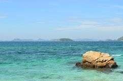 Beautiful calm sea with rock and mountain on blue sky day. Beautiful calm sea with rock and mountain on blue sky and sunny day Royalty Free Stock Photography