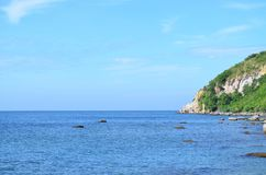 Beautiful calm sea with rock and mountain on blue sky day. Beautiful calm sea with rock and mountain on blue sky and sunny day Stock Photography