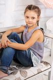 Beautiful calm smiling kid girl sitting on the bench in blue jea Royalty Free Stock Image