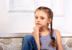 Beautiful calm thinking unhappy kid girl sitting on the bench in Royalty Free Stock Photography