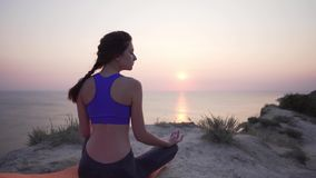 Beautiful and calm young girl practices yoga with her eyes closed - a static view from the back, morning by the ocean. Outdoor sports 4k stock video footage