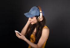Beautiful calm young woman in blue cap listening the music in wi Royalty Free Stock Photo