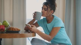 Beautiful, calm young woman with a cup of coffee, relaxing hot drink, happy lady holding a cup. Pretty brunette.Food and stock video footage