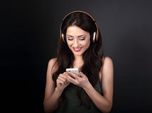Beautiful calm young woman listening the music in wireless headp Stock Photos