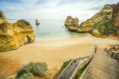 Beautiful Camilo Beach in the morning, Lagos, Algarve, Portugal. Beautiful Camilo Beach with wooden walkway descending to the sandy beach in Lagos, Algarve Stock Image