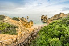 Beautiful Camilo Beach in the morning, Lagos, Algarve, Portugal. Beautiful Camilo Beach with wooden walkway descending to the sandy beach in Lagos, Algarve Stock Images