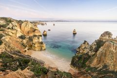 Beautiful Camilo Beach before sunrise, Lagos, Algarve, Portugal. Beautiful Camilo Beach with cliffs and arches in the morning, Lagos, Algarve, Portugal Royalty Free Stock Photography