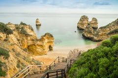 Beautiful Camilo Beach in the morning, Lagos, Algarve, Portugal. Beautiful Camilo Beach with wooden walkway descending to the sandy beach in Lagos, Algarve Stock Photography