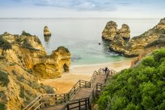 Beautiful Camilo Beach in the morning, Lagos, Algarve, Portugal. Beautiful Camilo Beach with wooden walkway descending to the sandy beach in Lagos, Algarve Royalty Free Stock Image