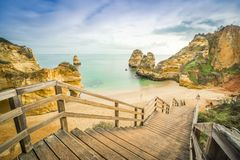Beautiful Camilo Beach in the morning, Lagos, Algarve, Portugal. Beautiful Camilo Beach with wooden walkway descending to the sandy beach in Lagos, Algarve Royalty Free Stock Images