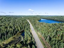 Beautiful Canada camper bus driving on road endless pine tree forest with lakes moor land aerial view travel background. Canada beautiful scenic camper bus royalty free stock photo