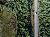 Beautiful Canada camper bus driving on road endless pine tree forest with lakes moor land aerial view travel background Royalty Free Stock Image