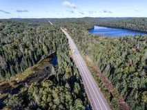 Beautiful Canada camper bus driving on road endless pine tree forest with lakes moor land aerial view travel background. Canada beautiful scenic camper bus stock photos
