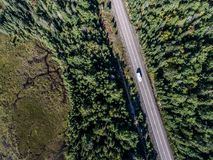 Beautiful Canada camper bus driving on road endless pine tree forest with lakes moor land aerial view travel background. Canada beautiful scenic camper bus stock photography