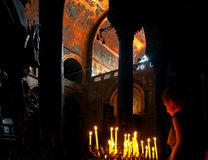Unidentified girl with lit candles in Basilica in Venice stock images