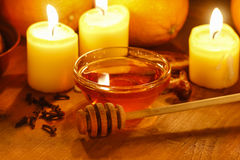 Beautiful candles, bowl of honey and fresh orange Royalty Free Stock Photography