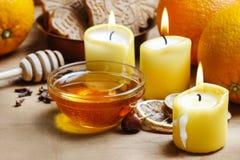 Beautiful candles, bowl of honey and fresh orange Stock Photography