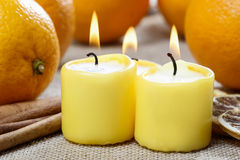 Beautiful candles and juicy oranges Stock Photos