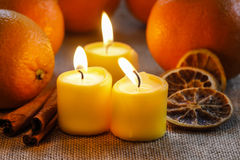 Beautiful candles and juicy oranges. On jute table cloth Stock Image