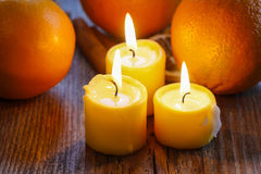 Beautiful candles and juicy oranges on jute table cloth Royalty Free Stock Photography