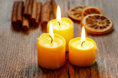 Beautiful candles and juicy oranges on jute table cloth Stock Photography