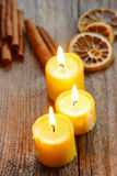 Beautiful candles and juicy oranges on jute table cloth Stock Images