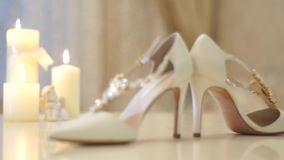 Beautiful candles with white ribbon and wedding shoes stock video footage