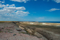 Beautiful canyon on the Ustyurt plateau аnd the Aral sea. Uzbekistan. Rocky shore cost Ustyurt, which resembles the Martian landscape. In the far background Royalty Free Stock Images