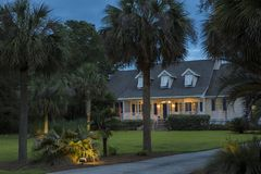 Beautiful cape cod house lit up at twilight. With palm trees royalty free stock images