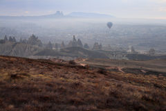 The beautiful Cappadocia. Sandstone formations and balloon in winter season. Uchisar view from the rose valley. Cappadocia, Turkey Stock Photo