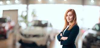 Beautiful car dealer consultant. Young woman consultant in showroom is standing near car Stock Photography