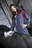 Beautiful Car Mechanic. A beautiful brunette model wearing a car mechanic uniform in a provocative pose, wiping the surface of a black car Stock Images