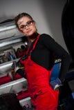 Beautiful Car Mechanic. A beautiful brunette girl in a car mechanic uniform, in a garage stock photos