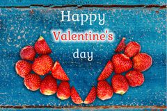 Beautiful card with a greeting on Valentine`s Day - heart strawberries on turquoise background textures and the words Happy royalty free stock photography