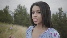 Beautiful carefree African American girl wearing long summer fashion dress enjoying stands on the field. Leisure of a. Portrait charming carefree African stock video