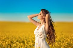 Beautiful carefree girl with long curly healthy hair over Yellow rape field landscape background. Attracive brunette with blowing royalty free stock photos