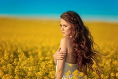 Beautiful carefree girl with long curly healthy hair over Yellow rape field landscape background. Attracive brunette with blowing royalty free stock image