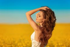 Beautiful carefree girl with long curly healthy hair over Yellow rape field landscape background. Attracive brunette with blowing royalty free stock photography