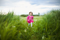 Beautiful carefree girl playing outdoors in field Stock Image
