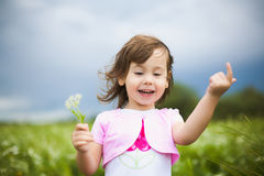Beautiful carefree girl playing outdoors in field Stock Photo