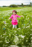 Beautiful carefree girl playing outdoors in field. With high green grass. little child running away from bubbles and laughing Royalty Free Stock Photo