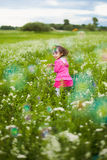 Beautiful carefree girl playing outdoors in field Stock Photos