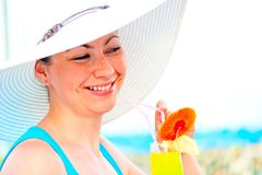Beautiful carefree girl in white hat with a cocktail in hand Stock Image