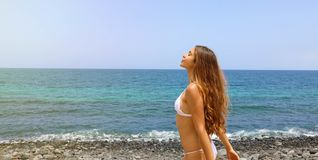 Beautiful carefree woman deep breath on the bech. Portrait of pretty young woman enjoying summer outdoors. Panoramic banner view royalty free stock image